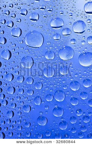 Blue water drops on the glass