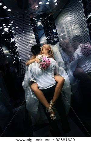 Wedding shot of sexy passion between bride and groom in lift