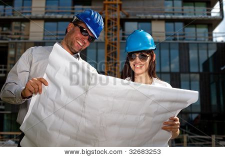 Construction Specialists Reviewing Bluprints At A Construction Site.