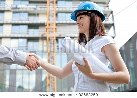 Young Female Construction Engineer Shaking Hands At Construction Site