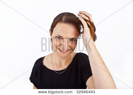 Attractive Young Woman Smiles And Plays With Her Hair