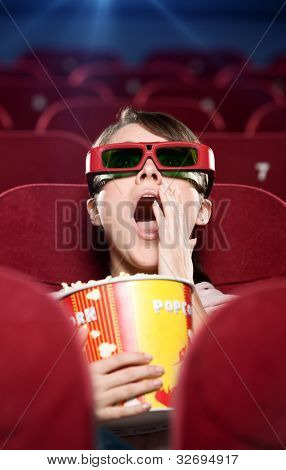 A surprised girl in 3D glasses watching a movie