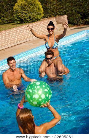 Happy young people playing in swimming pool, having fun.