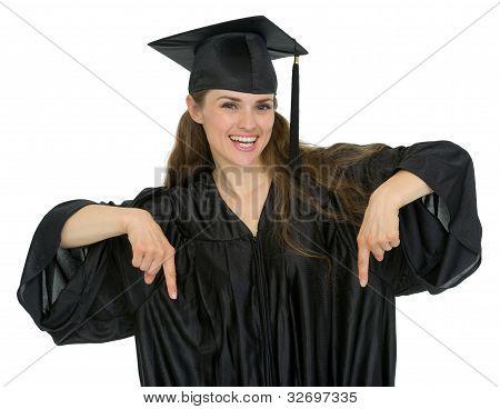 Feliz graduación estudiante mujer apuntando hacia abajo