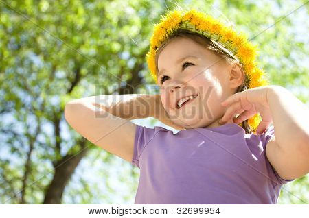Outdoor portrait of a cute little girl with dandelion wreath