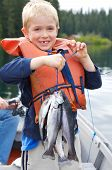 stock photo of toothless smile  - Little boy holding four trout with a big toothless smile - JPG