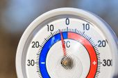 Outdoor thermometer with Celsius scale showing cold minus 4 degrees temperature - dramatic weather c poster