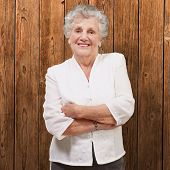 portrait of an adorable senior woman standing against a wooden wall