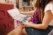 Mother Help Daughter Choose Interactive Book In Toy Store. Mom And Daughter Read Book In Library poster
