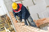 stock photo of mason  - construction mason worker bricklayer installing red brick with trowel putty knife outdoors - JPG