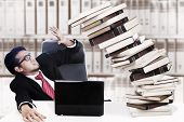 stock photo of collapse  - Scared businessman with stack of books which about to collapse - JPG