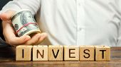 Wooden Blocks With The Word Invest And Money In The Hands Of A Businessman. Concept Of Investing In  poster