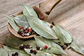 Dry Bay Leaf On A Wooden Table. Bay Leaf And Pepper Mixture In A Wooden Spoon poster