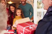 Grandparents Arriving With Gifts To Celebrate Multi-Generation Family Christmas At Home poster