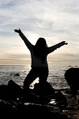 stock photo of plus size model  - Silhouette of a young woman posing on the beach with her arms up in the air - JPG