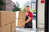 Portrait Of A Smiling Mover In Uniform Loading A Cardboard Boxes In A Moving Van poster