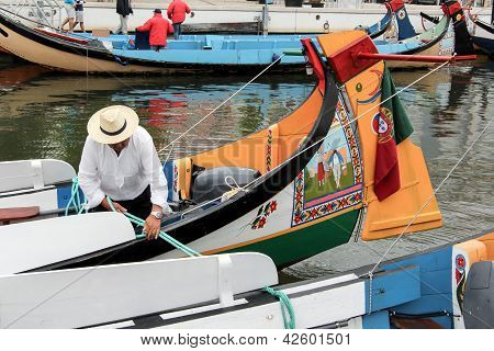 Portuguese Sailor Mooring Traditional Moliceiro Boat In Aveiro, Portugal