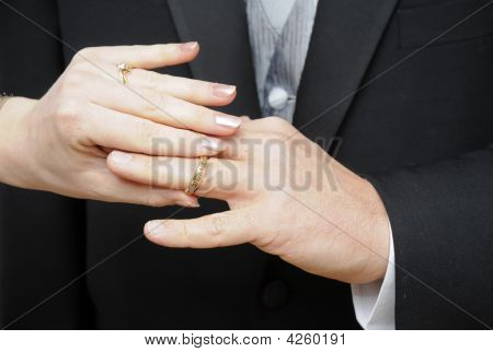 Bride Slipping Ring On Finger Of Groom