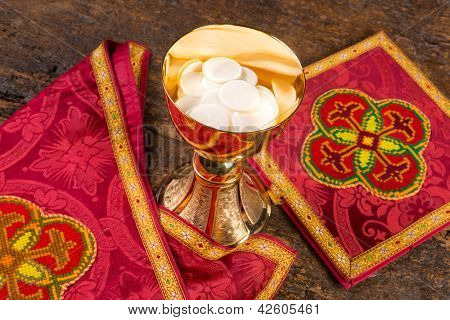 Communion scene of a chalice with vestment set and wafers