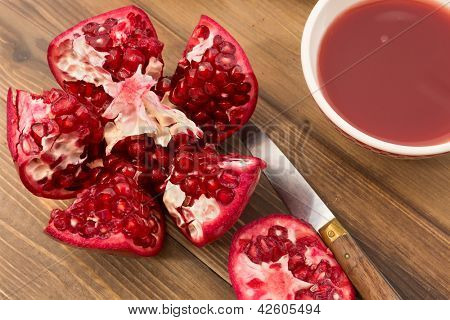 Detailed close up of a fresh pomegranate and bowl of juice