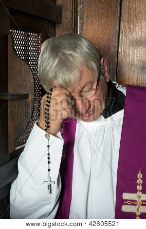 Vicar or priest sitting in a confession booth and listening to sins