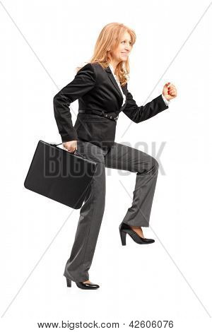 Full length portrait of a businesswoman with a briefcase making a big step isolated on white background