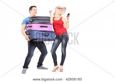 Jovem frustrado carregando bagagem de sua namorada enquanto ela está fazendo uma chamada