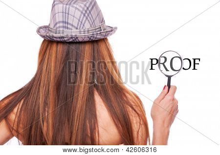 Long hair brunette with hat holding loupe and magnifying word proof