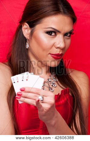 Attractive brunette in the red corset holding all aces in her hand, on the red background