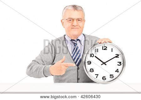 Mature man sitting and pointing on a wall clock isolated on white background