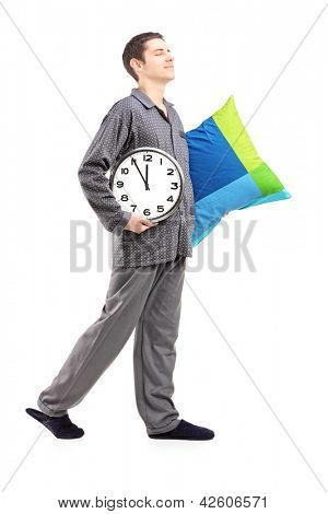 Full length portrait of a young man with pillow and clock sleepwalking isolated on white background