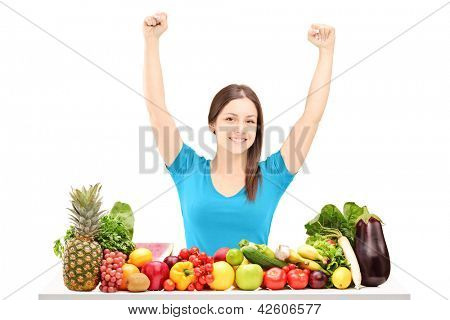 Beautiful young female gesturing happiness on a table full of fruits and vegetables isolated on white background