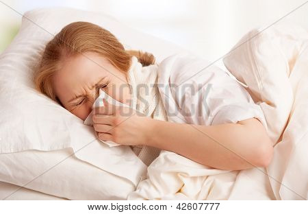 Ill Sick Young Woman Sneezes  Into A Handkerchief In Bed