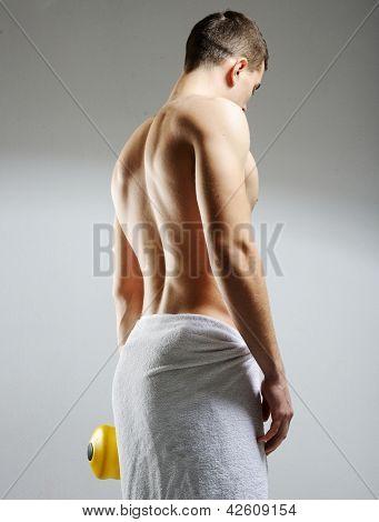 Vista posterior de un joven culturista masculino haciendo peso pesado ejercicio con pesas contra backgr oscuro