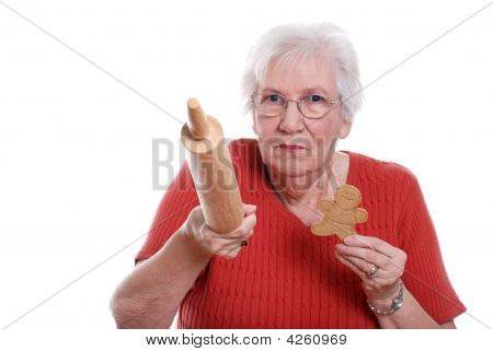 Senior Woman Protecting Gingerbread Men Cookies