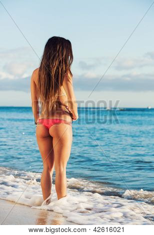 Beautiful young woman in bikini on beach at sunset