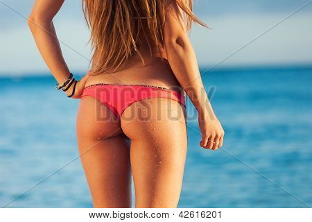 beautiful young woman in sexy bikini at the beach at sunset in Hawaii