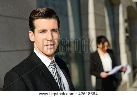 Attractive Young Businessmam And Businesswoman In Urban Background