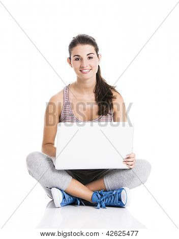 Beautiful student sitting in the floor with a laptop, isolated over a white background