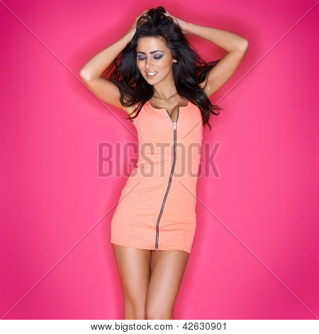 Beautiful sultry brunette in a skimpy miniskirt posing with her hand to her long tousled hair, three quarter studio portrait on pink