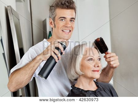 Portrait of hairstylist setting up female customer's hair in parlor