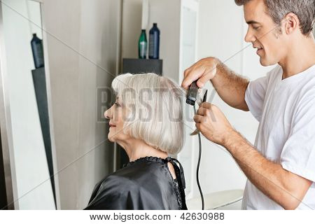 Side view of hairstylist straightening female customer's hair in beauty salon
