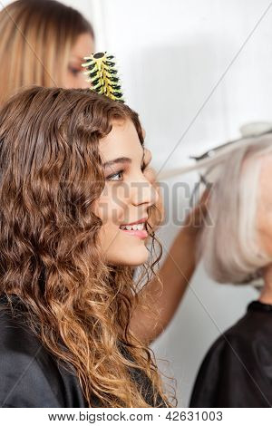 Side view of woman with hairdresser and client in the background at salon