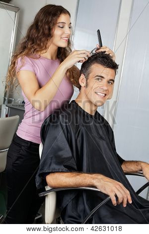 Portrait of happy mature client getting haircut in salon