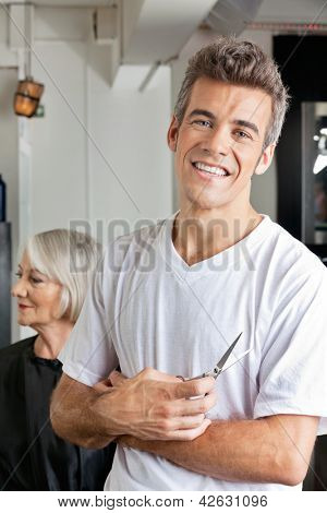 Portrait of happy male hairstylist holding scissors with female client in background