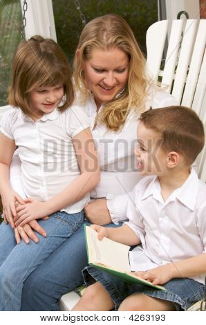 Young Boy Reads To His Mother And Sister
