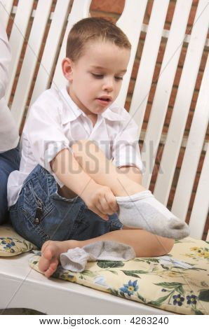 Adorable Young Boy Getting Socks On