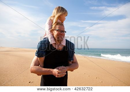 Father Carrying Daughter On Shoulders At The Beach