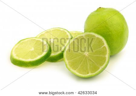fresh lime fruit and some thin slices on a white background