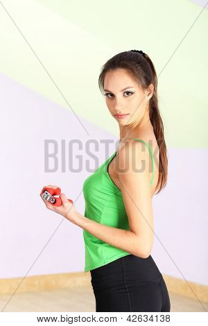 Young woman with carpal expander at gym